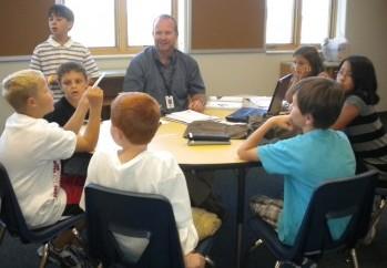 Groupe d'élèves et leur professeur utilisant le modèle de classe inversée