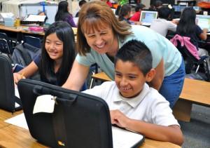 Le professeur a un rôle de tuteur et aide un élève sur un ordinateur lors d'une classe inversée