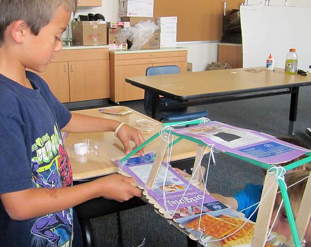 Des élèves construisent un pont suspendu dans leur classe inversée