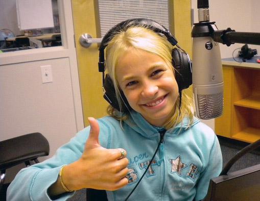 Sourire et pouce levé d'un élève qui anime la radio de l'école