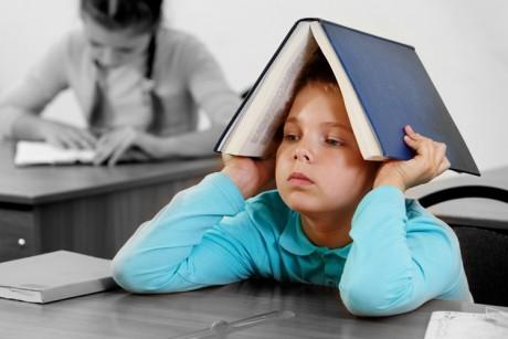 Elève qui s'ennuie en cours avec un livre sur la tête
