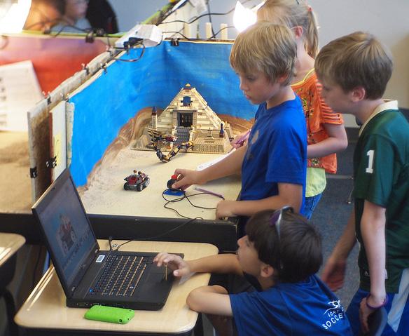élèves qui tournent un film sur ordinateur en classe